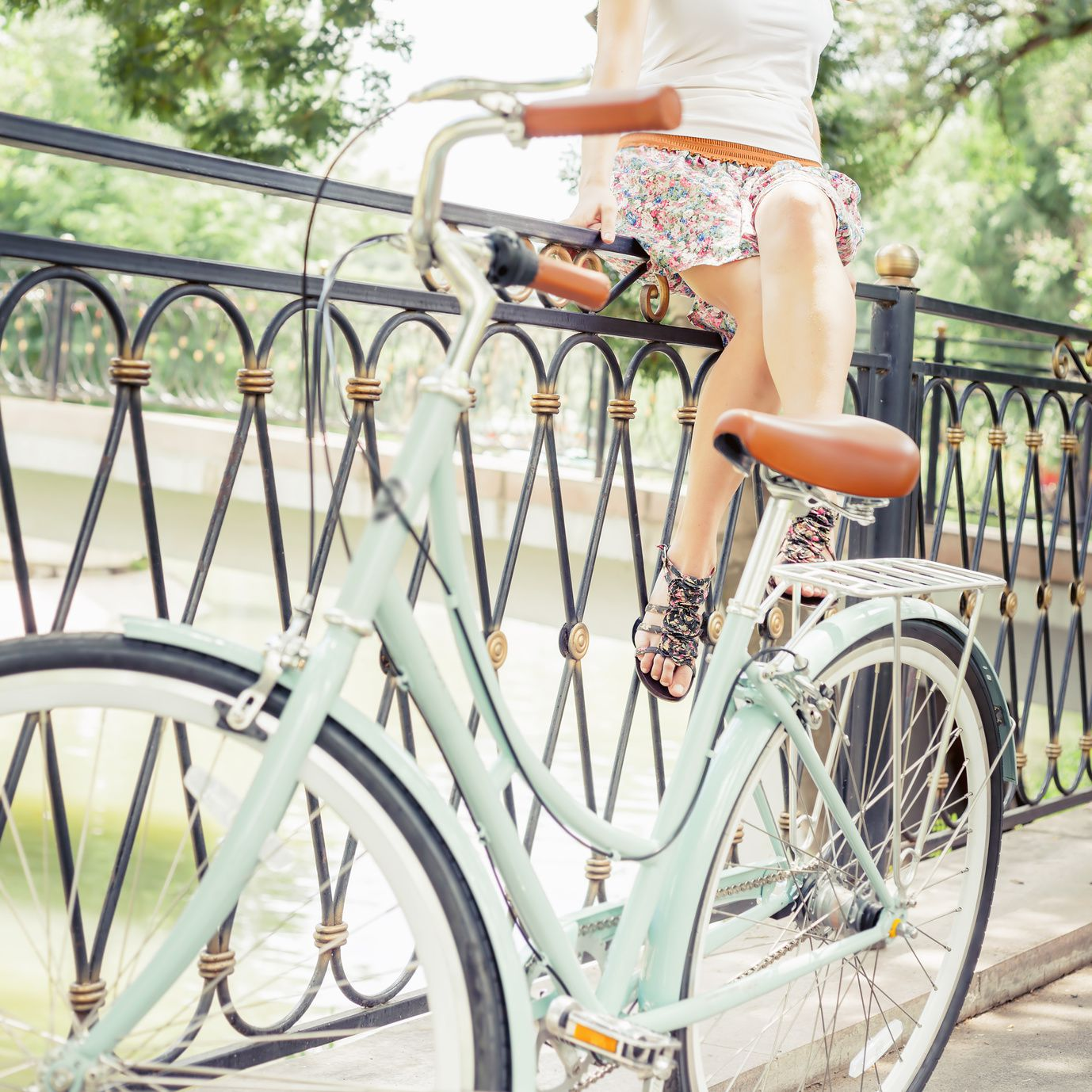 Young hipster girl sitting on fence near vintage city bike at the park. Freedom teenager with her happy vacation travel at European city, Paris